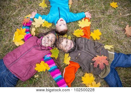 Three kids on grass with yellow leaves