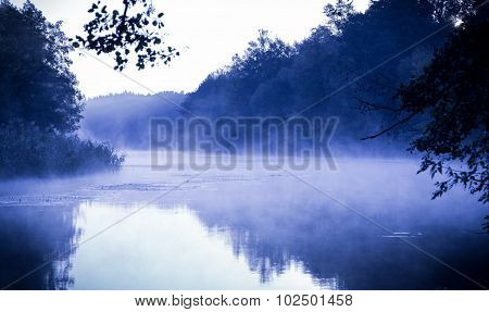Blue morning fog on a calm river