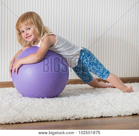 3-year-old  smiling girl with african braids on the ball for fittnesa at home