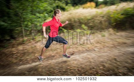 Young woman running outdoors in a forest, going fast (motion blurred image)