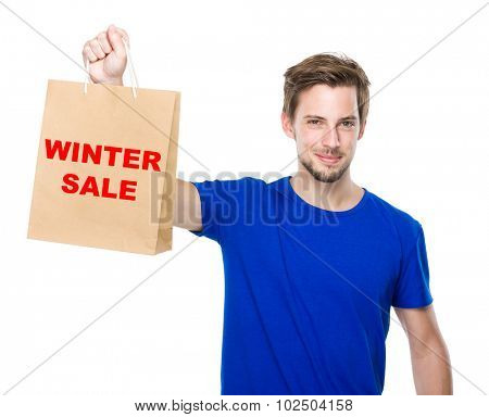 Young man hold with shopping bag and showing winter sale