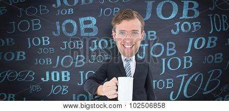 Geeky businessman holding mug against blackboard