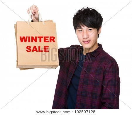 Asian Man hold with shopping bag and showing phrase of winter sale