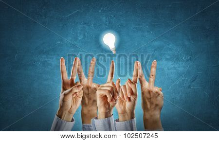 Word WIN with fingers and glowing light bulb