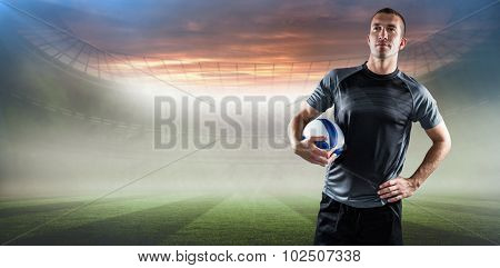 Rugby player holding ball with hand on hip against rugby pitch