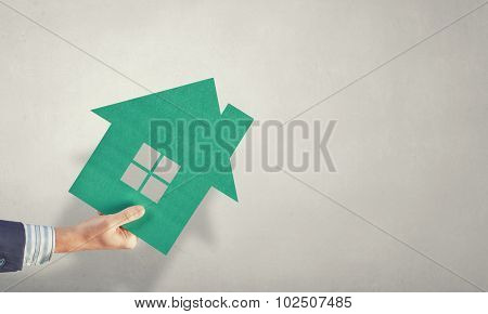 Hand of business person holding house card
