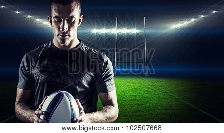 Thoughtful rugby player holding ball against rugby stadium