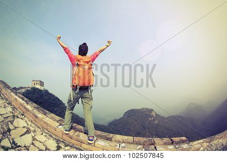 cheering woman hiker open arms on chinese great wall