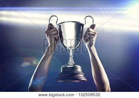 Successful rugby player holding trophy against spotlights