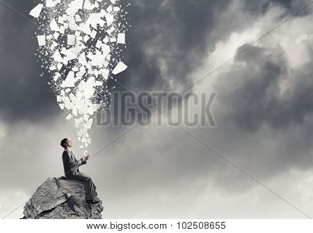 Young businessman sitting on rock top with mobile phone in hand