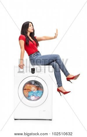 Vertical shot of a young woman waiting for the washing machine to finish the laundry and meanwhile looking at her fingernails isolated on white background