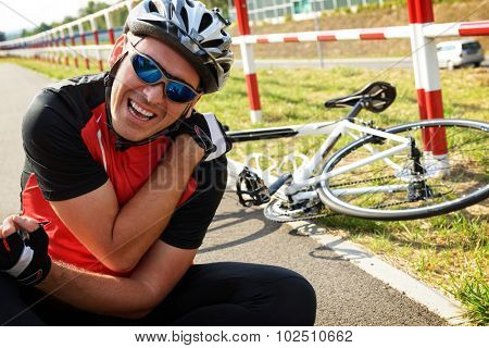 Bicycle accident. Biker holding his shoulder.