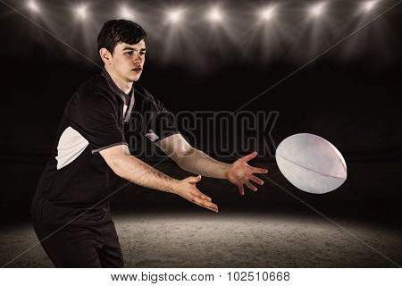 Rugby player throwing a rugby ball against spotlight and pitch