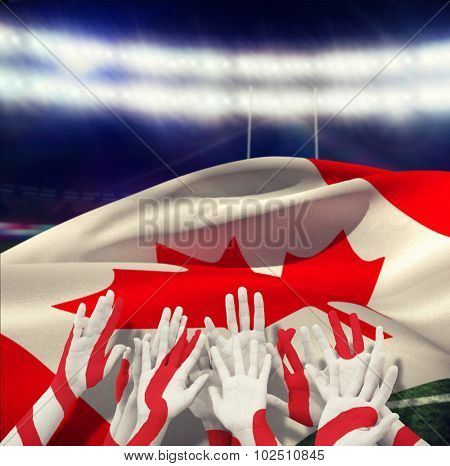 People raising hands in the air against rugby stadium