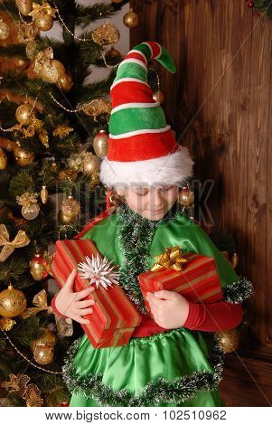 Girl in suit of Christmas elf with a gift