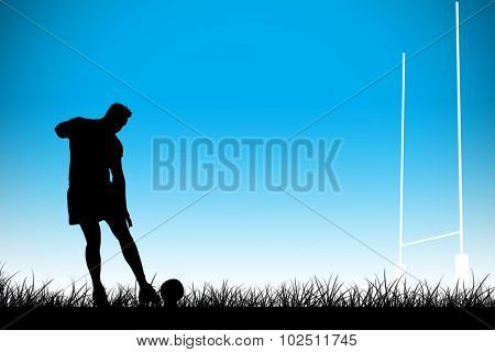 Rugby player ready to kick against blue background with vignette