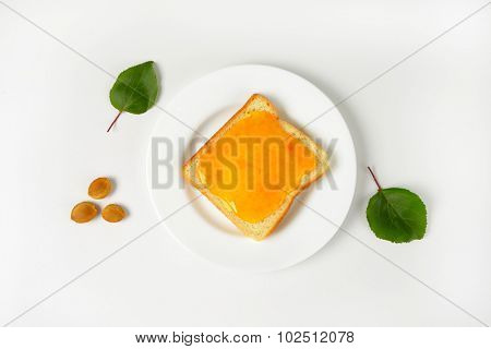 overhead view of white toast with apricot jam served on the plate and with three apricot stones next to