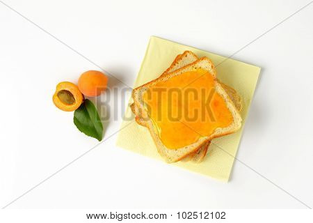 overhead view of white toast greased with apricot marmalade and accompanied by fresh halved apricot