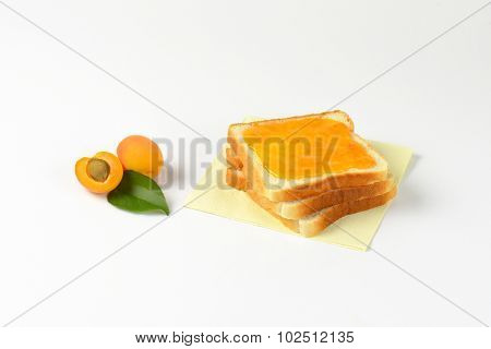 three stacked white toasts with apricot jam on the top and accompanied by halved apricot with stone