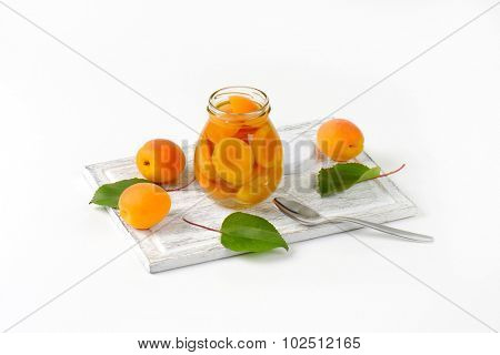 apricot compote in the glass jar standing on the wooden cutting board and surrounded by fresh apricots and leaves