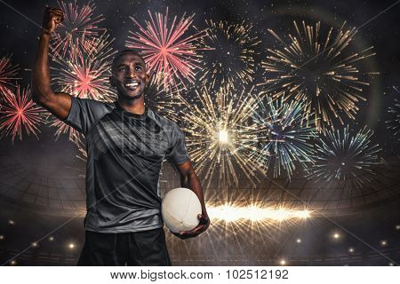 Happy sportsman with clenched fist holding rugby ball against fireworks exploding over football stadium