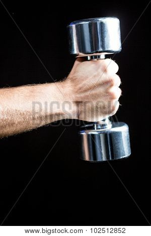 Close-up of of man working out with dumbbell against black background