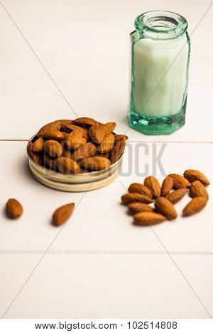 Almonds in a lid with milk jar on the table