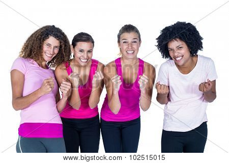 Portrait of smiling group of women with clasped hands while standing against white background