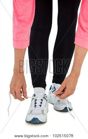 Low section of woman tying shoelace on white background