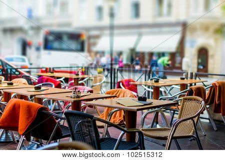 treet view of a Cafe terrace with tables and chairs in european city. Toned photo. soft focus