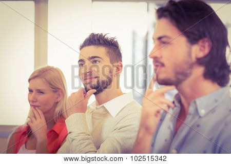 Business people day dreaming with hand on chin in creative office