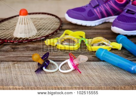 Pacifier and sports equipment. Concept of sports to be engaged with early childhood.
