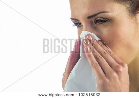 Close-up of sick woman with tissue on mouth against white background
