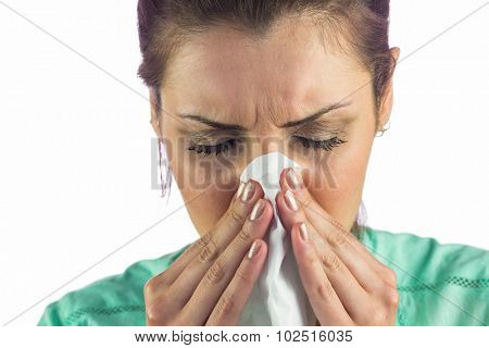 Close-up of woman suffering from cold with tissue on mouth against white background