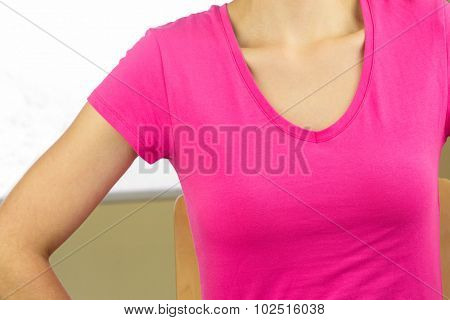 Mid section of woman wearing pink top while sitting on chair at home