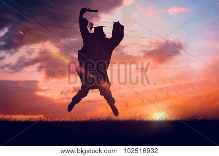 Male student in graduate robe jumping against orange and blue sky with clouds