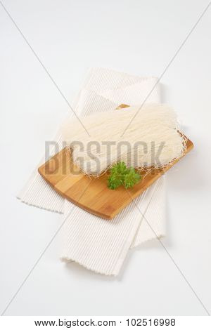 rice noodles on wooden cutting board and white place mat
