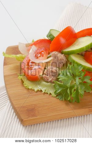 close up of fresh vegetables with tuna chunks on wooden cutting board and white place mat