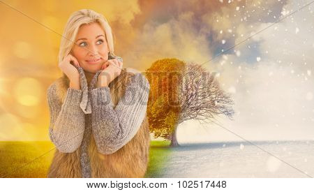 Blonde in winter clothes smiling against autumn changing into winter