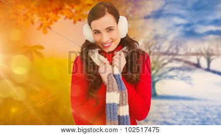Happy brunette in winter clothes smiling at camera against autumn changing to winter