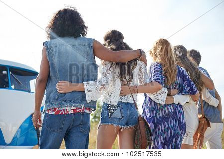 summer holidays, road trip, vacation, travel and people concept - young hippie friends hugging over minivan car from back