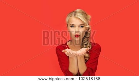 people, holidays, christmas, valentines day and advertisement concept - lovely woman in red dress blowing something on palms of her hands over red background