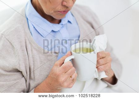 health care, flu, cold, age and people concept - close up of sick senior woman with paper napkin drinking hot tea at home
