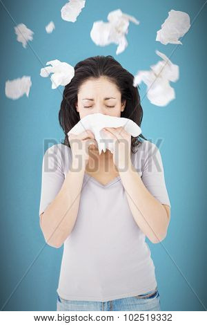 Sick brunette blowing her nose against blue background