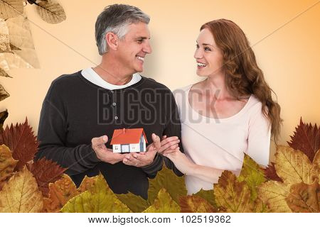 Casual couple holding small house against autumn leaves pattern