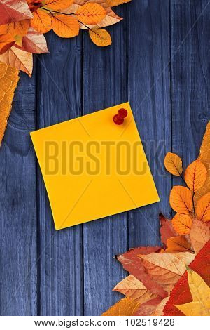 Digital image of pushpin on yellow paper against autumn leaves on wood