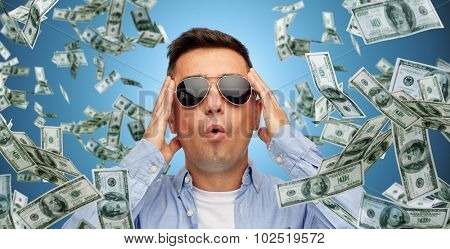 business, finance, luck, fortune and people concept - face of scared or surprised middle aged latin man in sunglasses over blue background with heap of falling dollar money