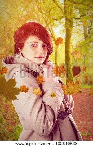 Portrait of beautiful woman wearing winter coat against peaceful autumn scene in forest