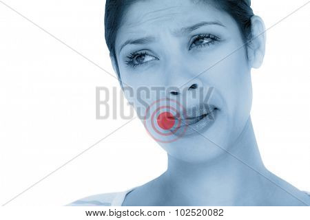 Beautiful woman licking lips while looking away against highlighted pain