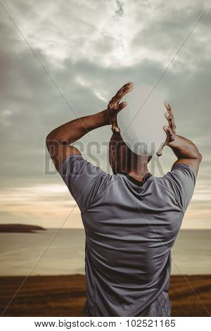 Rear view of sportsman throwing rugby ball against grey sky over ocean